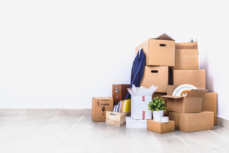 Move. Cardboard boxes in empty room corner.